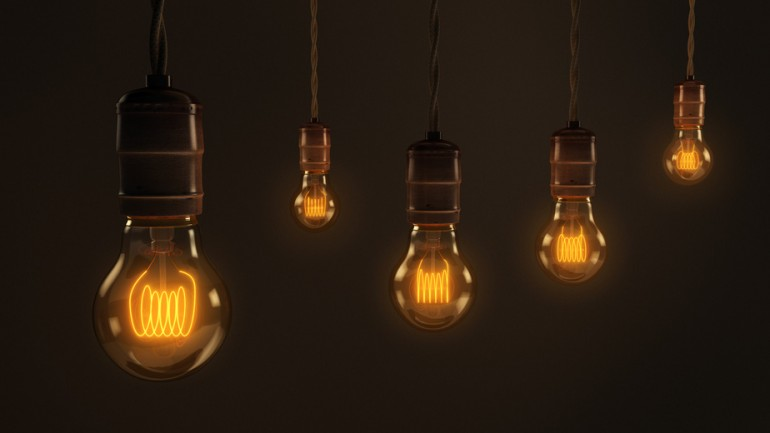 A quintet of vintage hanging light bulbs over a dark brown background